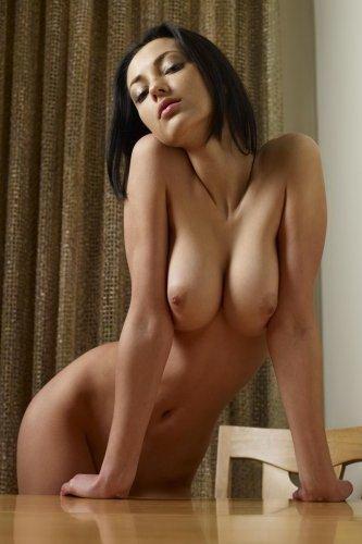Голая брюнетка с сексуальным телом делает эротические снимки на столе